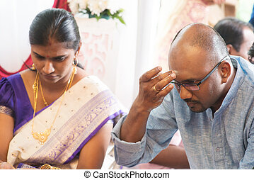 Hindu man putting tilak or marking on his forehead during...