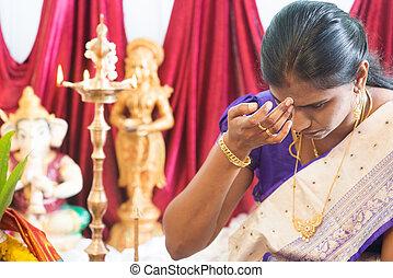 Hindu woman putting bindi or marking on her forehead during...