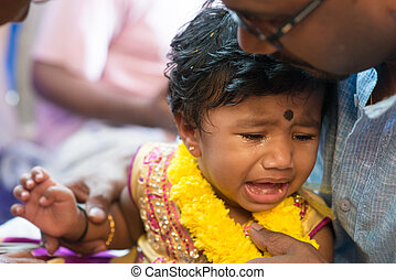 Baby girl crying in ear piercing ceremony - Father pampered...
