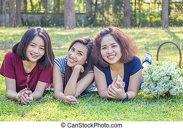 women lying on grass in park - Three Asian woman lying on...