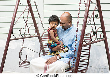 Indian father and daughter sitting on a swing. Traditional...