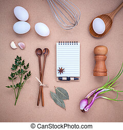 Four white eggs with note book ,pepper bottle ,wooden spoons ,bay leaf parsley and wire whisk set up on brown background.