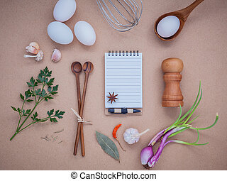 Four white eggs with note book ,pepper bottle ,wooden spoons...