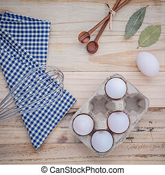 Cardboard egg box with eggs ,pepper bottle ,wooden spoons ,bay leaf and wire whisk set up on old wooden background.