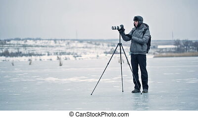 photographer with tripod in winter - professional...