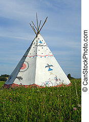 tipi on green meadow on background of blue sky