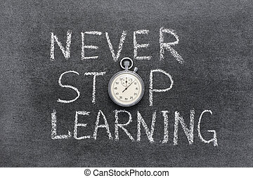 never stop learning phrase handwritten on chalkboard with...