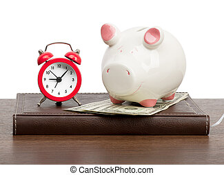 Alarm clock with piggy bank on personal organizer on white
