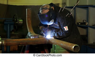 Welder at work in industrial factory
