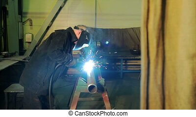 Welding process in industrial factory - Welder at work in...