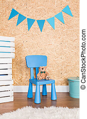 Childish blue chair and teddy bear, chipboard wall in...