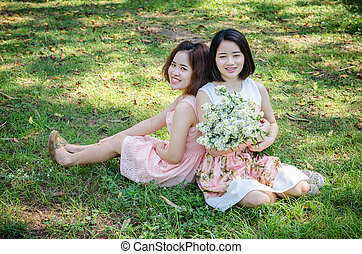 woman sitting on grass in park - Young Asian woman sitting...