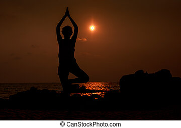 man silhouette in yoga pose against sun disk over sea -...