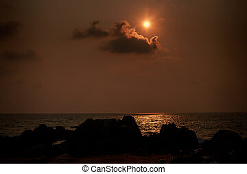 sun disk near cloud over sea at sunrise dark rock on...