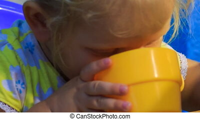 closeup small blonde girl drinks from yellow cup - closeup...