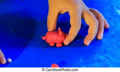 kid's hands play with blue toy pig of plasticine on blue...
