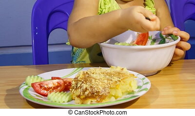 closeup little blonde girl eats soup vegetables