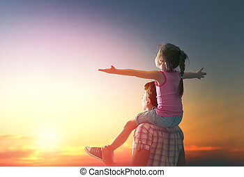 happy family at sunset. father and daughter having fun and...