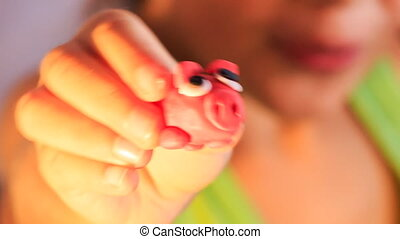 girl shows in hand sculptured pink toy pig closeup