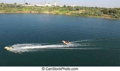 Jet Ski Pulling Inflatable Raft With A Man On Lake,...