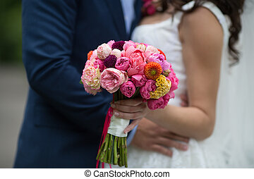 Wedding bouquet of freshly cut flowers closeup with bride and groom in background