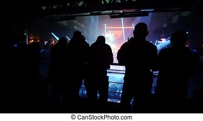 Group of people stay on second floor of a nightclub and watch down on a crowd.