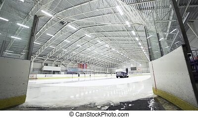 Big blue ice resurfacer truck polishes covered ice rink -...