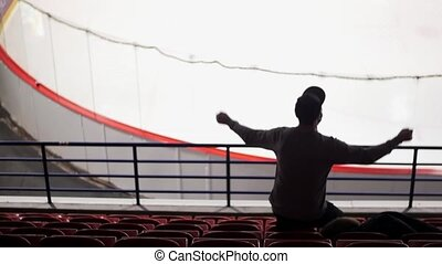 Back side of one hockey fan on tribune, who jumps and rises handes. Slow motion