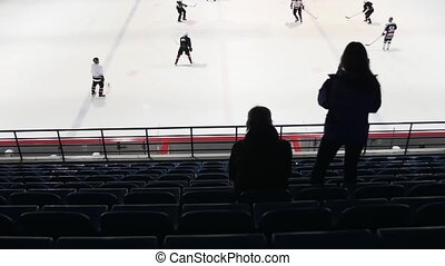 Back side of two hockey fans on tribune watching the game. Slow motion