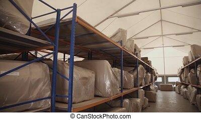 Big bags in cardboard lie on wooden shelves in storage. Pan horizontal