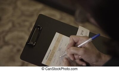 Woman's hands holds a black folder and fills a document on...