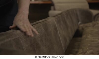 Man go around big sofa and check it in furniture factory