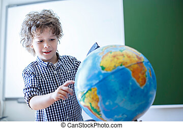Pupil with a globe in class