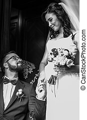 Happy handsome groom on leather chair holding the hand of a...