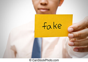 fake - Fake word on  yellow card holding by businessman.