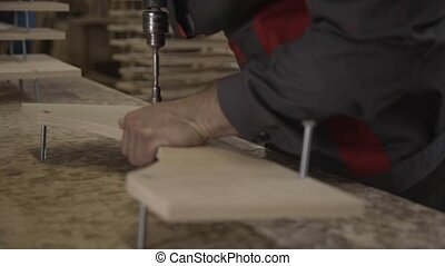 Man in uniform twists long bolts in wooden board by drill in furniture factory.
