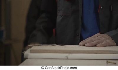 Man puts sheathing around prepared wooden board by staple...