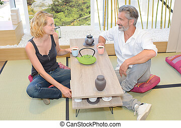 Man and lady sat on cushions drinking coffee