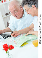 Elderly couple planning voyage on map
