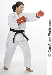 Left punch - woman wearing a karate uniform and red boxing...
