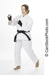Fighting position - woman wearing a karate uniform throwing...