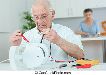 Elderly man using multi meter on electrical appliance