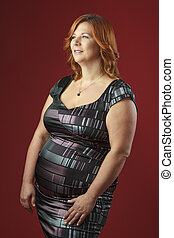 Plus size model - plus size fashion model against a red...