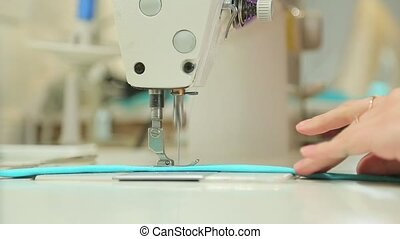 Woman doing a flat line on the sewing machine.