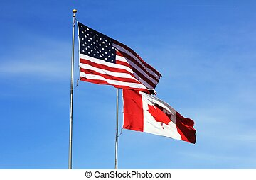 USA and Canadian flags flying side-by-side - American and...