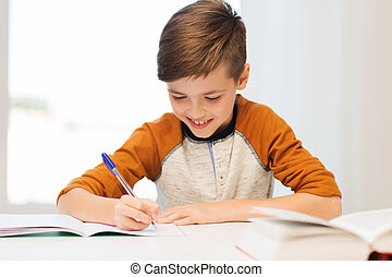 smiling student boy writing to notebook at home - education,...