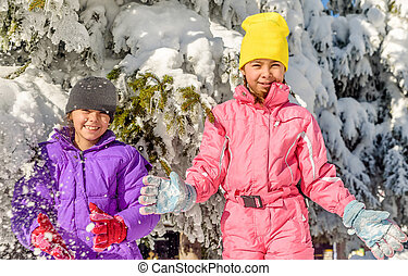 Two little girls are having fun in the snow
