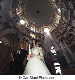 Religous couple, bride and groom, holding candles in baroque...