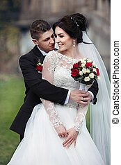Sensual romantic groom hugging beautiful bride from behind with a bouquet