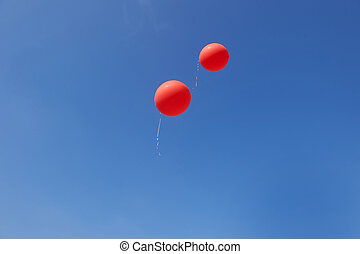 Two red balloons flying in a blue sky